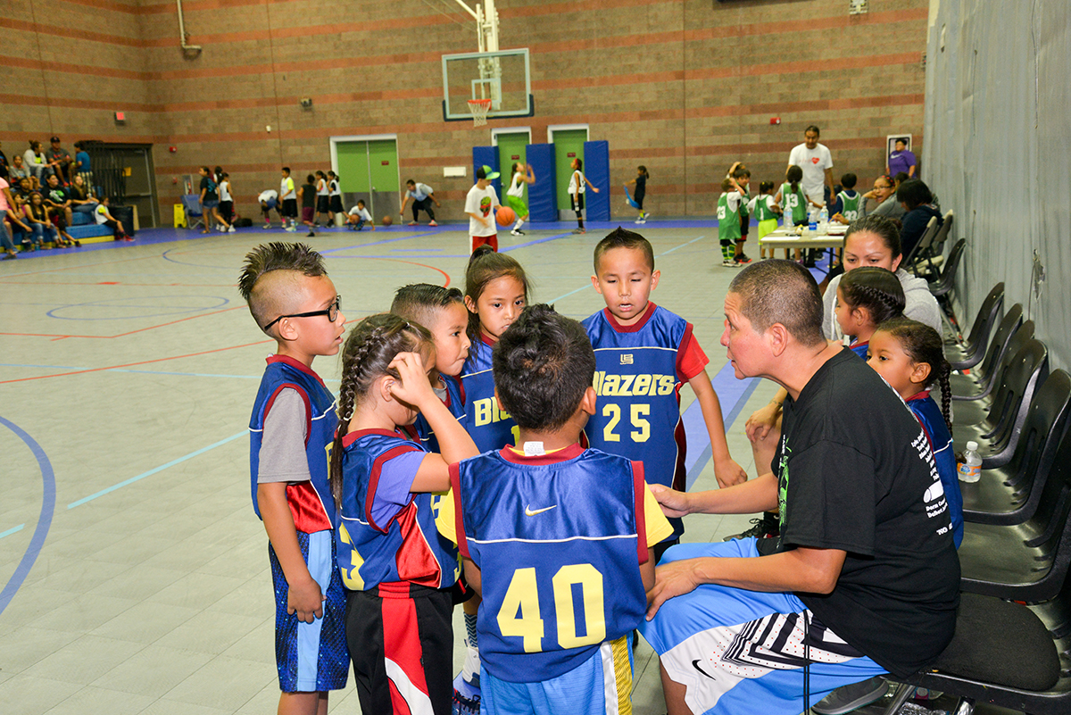 Becenti gives basketball pointers to the Lil' Blazers during a timeout.